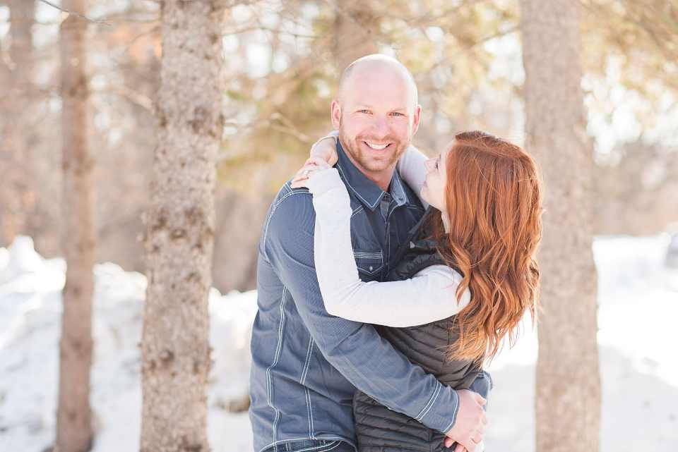 A redhead smiles up to her fiance during their sunny winter engagement session