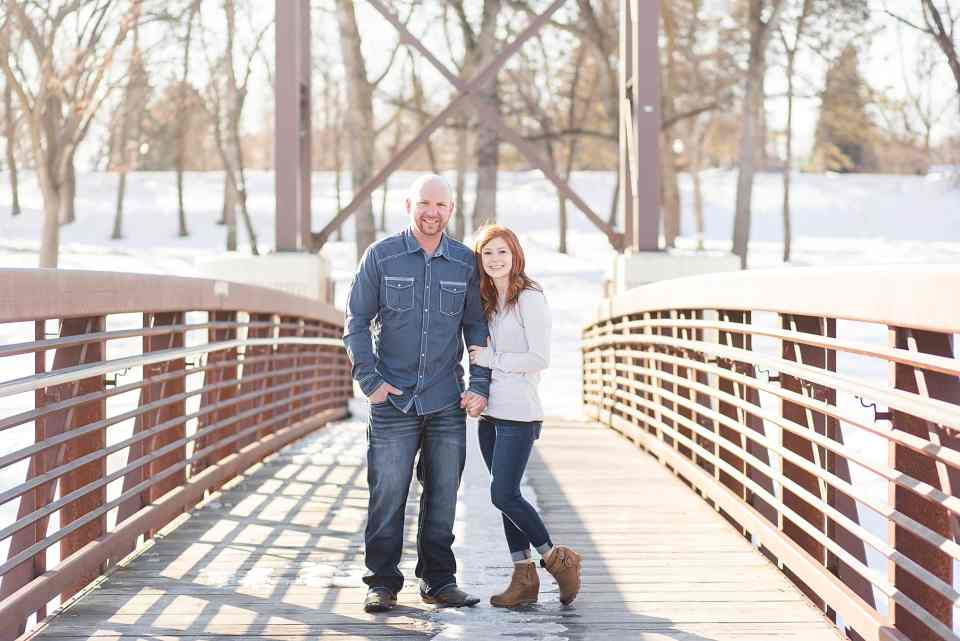 A tall man in blue and his redhead fiancee hold hands and smile on the Lindenwood bridge in Fargo