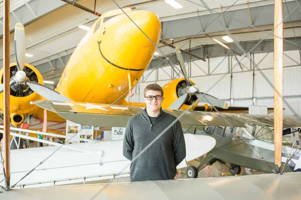High school senior in grey sweatshirt smiles in front of a yellow plane during his Senior Session at Fargo Air Museum
