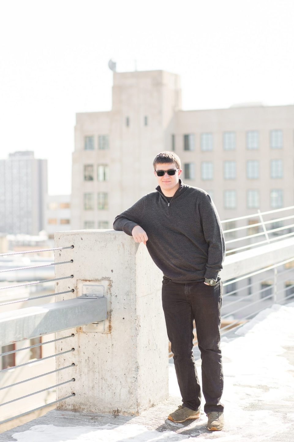 A senior guy leans on a concrete post in Downtown Fargo for his high school senior session