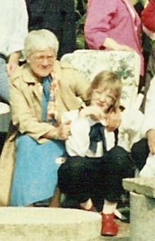 Oma sitzt auf einem Gartenstuhl, im Vordergrund kniee ich, sie hat ihren Arm um meine Schulter gelegt und hält mich mit ihrer anderen Hand am Oberarm. Ich trage knallrote Lederschuhe und eine viel zu große Brille. Es waren die 80er, was soll ich sagen^^