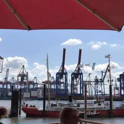 Aufnahme aus dem Restaurant direkt an der Elbe, im Vordergrund eine Markise, dann fängt auch schon das Wasser an, im Hintergrund ein paar Kräne des Hafens