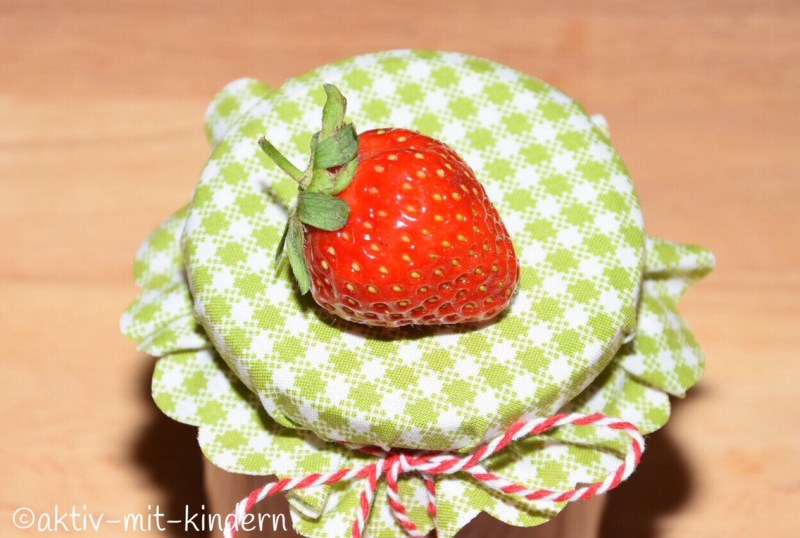 Unsere selbstgemachte Erdbeermarmelade. Dekoriert mit einer frischen Erdbeere.