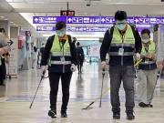 Pekerja bermasker melakukan kegiatan desinfeksi di area Bandara Internasional Taoyuan, Taiwan