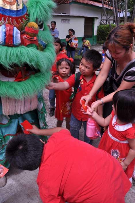Anak-anak memberikan angpao lewat mulut Barongsai