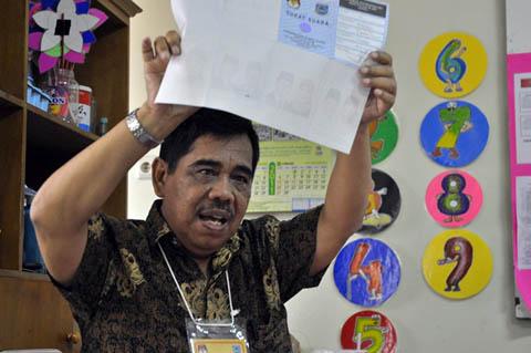 H. Syukri, Ketua KPPS TPS 21 sedang membacakan hasil pencoblosan dari Surat Suara 1