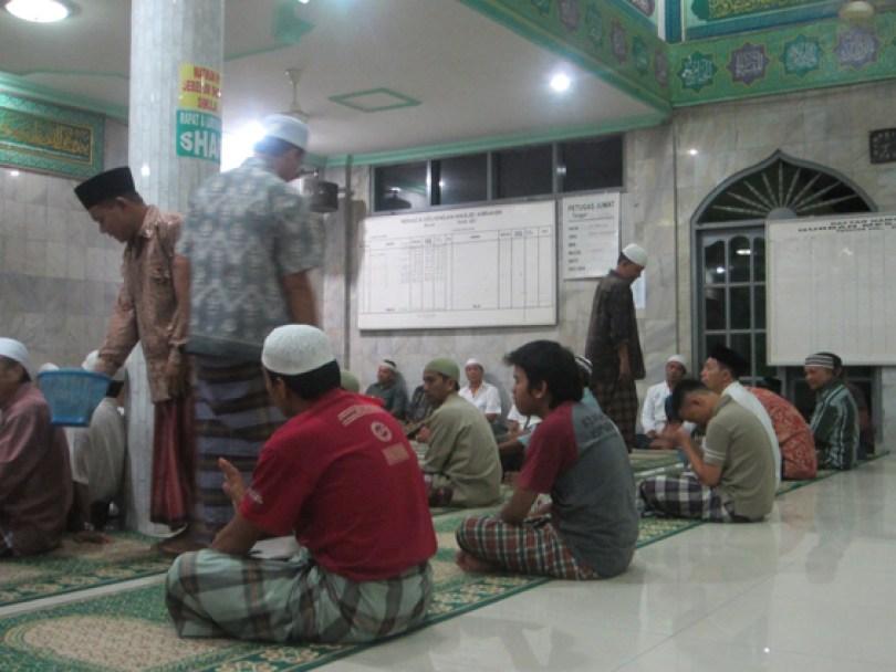 Panitia masjid mengumpulkan infak dari jamaah.