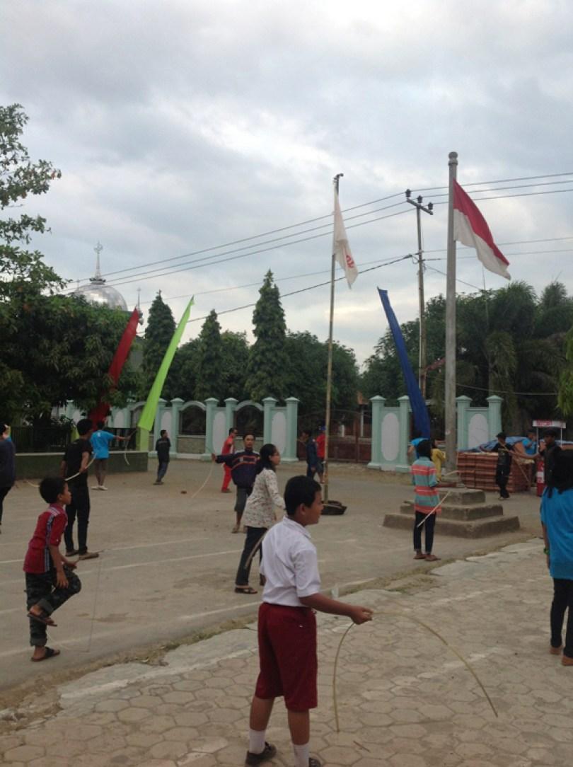 Anak-anak dan orang dewasa ikut serta memainkan musik angin.