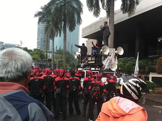 Rombongan massa buruh. Tampak di foto, mobil panggung yang meggunakan pengeras suara.
