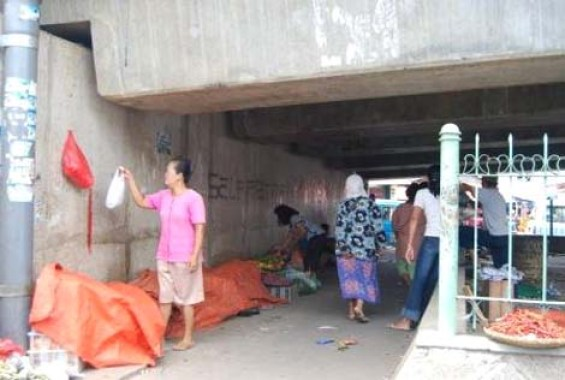 The sidewalk traders along the street which should have become a pedestrian crossing under the flyover.