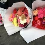 ビニールのスリーブに入れて簡易包装紙にて包んだカーネーション花束のお届け