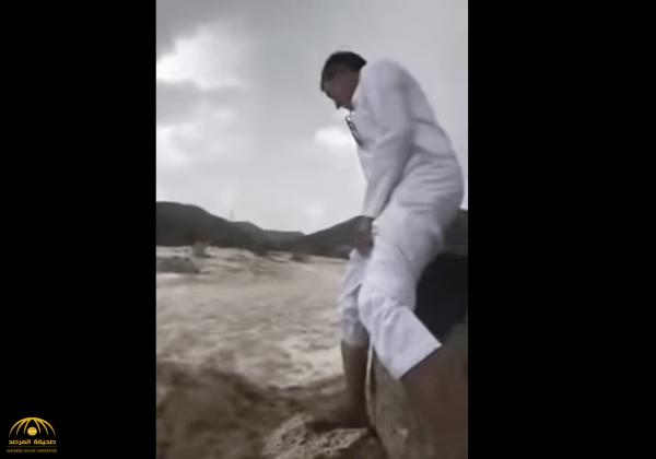 شاهد فيديو مروع : شاب يقع في وادي ببيشة وتجرفه المياه .. وهذا ما حدث له!