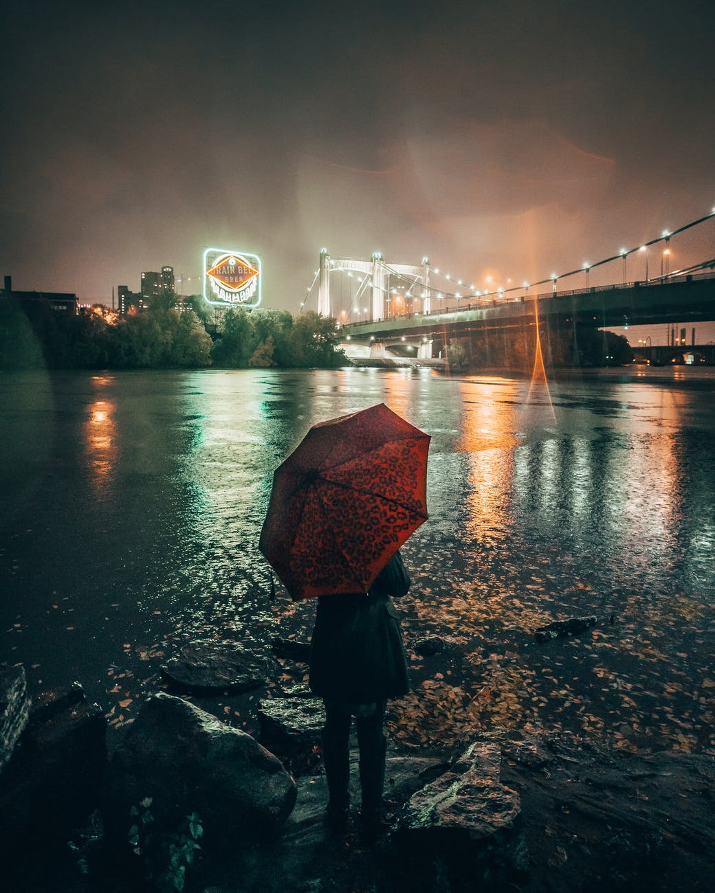 woman with red umbrella standing at riverbank