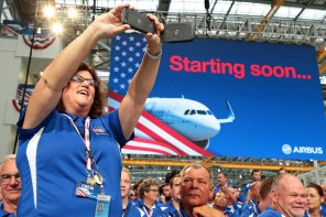 Airbus employee Jennifer Ogle of Fairhope, Ala., documents the activities at the grand opening ceremony of Airbus U.S. Manufacturing Facility is held Monday, Sept. 14, 2015, in Mobile, Ala. (Mike Kittrell/Alabama NewsCenter)