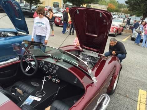 Crowds gather around classic cars.