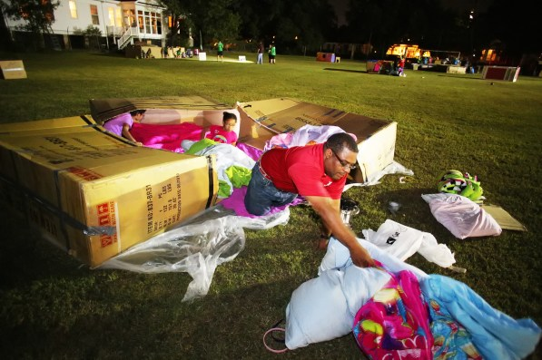 LaBarron McCaskey and his daughters Joia, 10, and Aria, 6, of Mobile prepare their shelter for Cardboard City. (Mike Kittrell/Alabama NewsCenter)