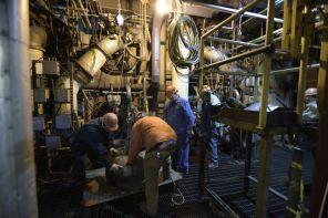 Workers take apart a burner