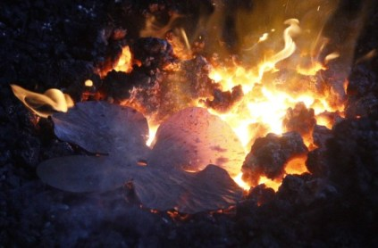 Metal poppy petals are heated in a coal fire as part of a project by Alabama blacksmiths in Athens Forge to contribute to a World War I memorial to be erected in Ypres, Belgium. (contributed)