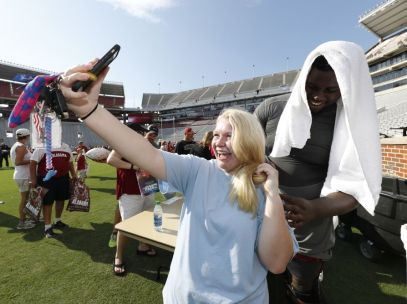 Players and coaches sign autographs during Fan Day at the University of Alabama football practice. (Robert Sutton / Alabama NewsCenter)