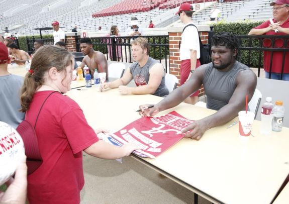 Defensive lineman Dalvin Tomlinson signs autographs during Fan Day. (melia B. Barton / UA Athletics)