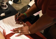 Marquetta Hill-King signs over the first car to Bianca Donerson in the first-ever Wheels of Change giveaway for the Willie J. Foundation. (Solomon Crenshaw Jr. / Alabama NewsCenter)