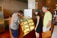 Seaborn Whatley, left, tells visitors Beckie and Iander Allen from Arlington, Va., about the Pie Lab pies. (Karim Shamsi-Basha / Alabama NewsCenter)