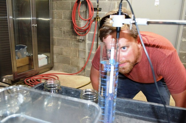 Stephen Watts, co-founder of Redmont Distilling, measures the alcohol level in gin. (Michael Tomberlin / Alabama NewsCenter)