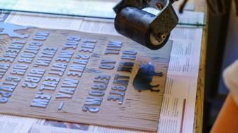 Riffe applies ink to the linoleum in preparation for printing. (Mark Sandlin/Alabama NewsCenter)