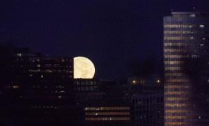 The moon, or supermoon, is seen from Washington as it sets behind buildings in Arlington, Va. (Joel Kowsky/NASA)