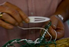 Henry Barnes works on a net in Steve Sprinkle's shop. Intricate handwork makes the nets strong. (Karim Shamsi-Basha/Alabama NewsCenter)