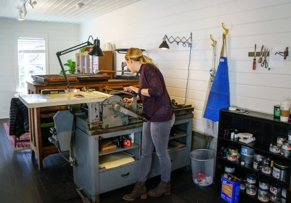 Bradey Baxter, letterpress specialist at After Press in Homewood, works with a 1950s Vandercook machine. (Mark Sandlin/Alabama NewsCenter)