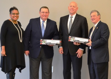 Publix officials Brenda Reid, left, and Mike Smith, second from right, present model Publix trucks to Jefferson County Commission President Jimmie Stephens, right, and Rick Davis, senior vice president of economic development with the Birmingham Business Alliance. (Michael Tomberlin / Alabama NewsCenter)
