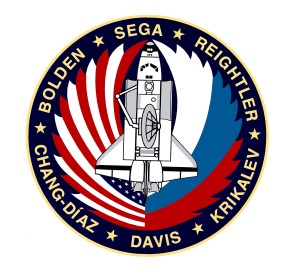 The design of the crew patch for NASA's STS-60 mission depicts the Space Shuttle Discovery's on-orbit configuration. The American and Russian flags symbolize the partnership of the two countries and their crew members taking flight into space together for the first time. The open payload bay contains: the Space Habitation Module (Spacehab), a commercial space laboratory for life and material science experiments; and a Getaway Special Bridge Assembly in the aft section carrying various experiments, both deployable and attached. A scientific experiment to create and measure an ultra-vacuum environment and perform semiconductor material science -- the Wake Shield Facility -- is shown on the Remote Manipulator System (RMS) prior to deployment. (NASA).