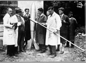 "Historic view of the Verein Fuer Raumschiffahrt, 1930. Left to Right: Rudolf Nebel, Franz Ritter, unknown, Kurt Heinisch, unknown, Hermann Oberth, unknown, Klaus Riedel, Wernher von Braun, unknown. Klaus Riedel holds early version or model for the minimum rocket, 'Mirak."" Marshall Space Flight Center, Redstone Rocket (Missile) Test Stand, Huntsville, AL. (Library of Congress Prints and Photographs Division)"