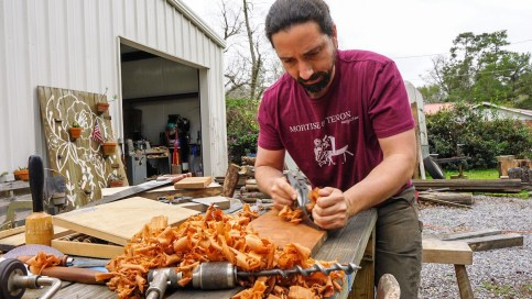 Shannon Brantley works a wood plane on the latest Flannel and Floral creation. (Mark Sandlin / Alabama NewsCenter)
