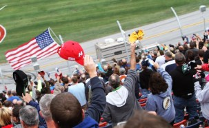 Racing fans cheer as Johnny Ray makes his iconic drive-by in his diesel big-rig, decked out with a giant American Flag, before a race at Talladega Superspeedway. The tradition began in 2001, the year that brought the Sept. 11 terrorist attacks and the death of NASCAR legend Dale Earnhardt Sr. (Talladega Superspeedway)