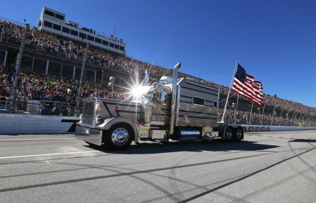 Johnny Ray makes his iconic drive-by in his diesel big-rig, decked out with a giant American Flag, before a race at Talladega Superspeedway. The tradition began in 2001, the year that brought the Sept. 11 terrorist attacks and the death of NASCAR legend Dale Earnhardt Sr. (Talladega Superspeedway)