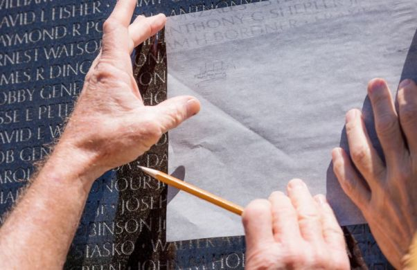 The Tuscaloosa Rotary Club gave veterans tracing paper so to trace the names of lost comrades. (Simo Ahmadi/Alabama NewsCenter)