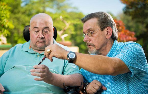 Miller's (left) mentor gives tips on developing motor skills. (Phil Free/Alabama NewsCenter)