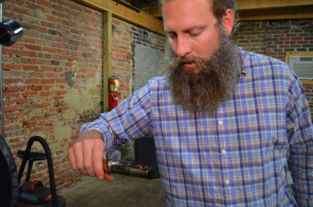 Ryan Bergeron's checks the roast at Revival Coffee Company in Selma. (Michael Tomberlin / Alabama NewsCenter)