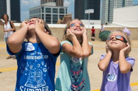 Parker, Emma, and Cecilia Misso of Trussville watch the eclipse at McWane Science Center. (Phil Free / Alabama NewsCenter)