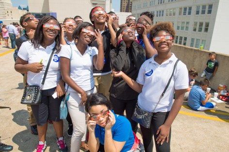 Fairfield High School students Shaniah Nunn, Cumesha Stoves, Alexis William, Janyah Farahkhan, Aaliyah Gradson, Glory Brown, Nylah Campbell, Jerkhya Thomas, Kevin Guans, Kanyce Patterson, Jayvcon Fleming, Tobias Cathey, Karim Beonbery and Andre Jones watch the solar eclipse at McWane Science Center. (Phil Free / Alabama NewsCenter)