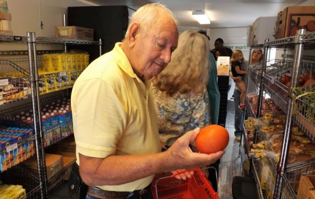 Ernest Wattenberger considers a tomato. (Donna Cope/Alabama NewsCenter)