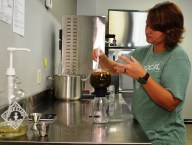 Mandy Nobles blends tea in the Piper & Leaf store in Birmingham's Woodlawn neighborhood. (Michael Tomberlin / Alabama NewsCenter)