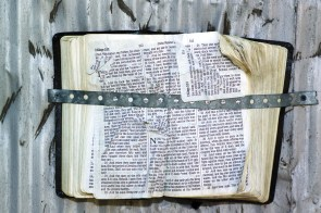 Linemen doing storm restoration work see some unusual sights. Here, a Bible is strapped to a metal wall following Hurricane Ivan. (File)