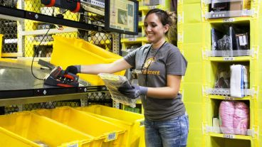 "An Amazon employee sorts merchandise for shipping. The company plans to open a ""sortation center"" in Mobile. (Amazon)"