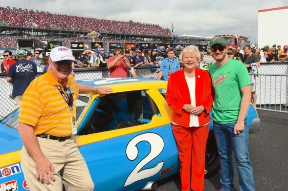 Dale Earnhardt Jr. poses with Gov. Kay Ivey and his father's Monte Carlo. (Karim Shamsi-Basha / Alabama NewsCenter)