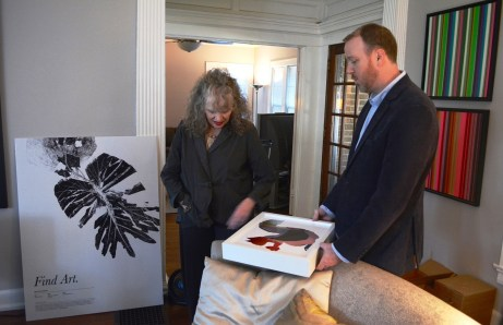 Eileen and Alex Kunzman discuss a mixed media piece by Darrel Ezekiel.(Karim Shamsi-Basha / Alabama NewsCenter)