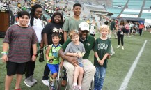 Tim Alexander, seated, poses with a group of Children's Harbor patients who were honored with having their names on the backs of UAB football jerseys at the Blazers' homecoming game. Alexander, the face of the return of UAB football, was the first-ever paraplegic to get a scholarship in Division I football. (Solomon Crenshaw Jr./Alabama NewsCenter)