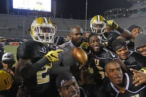 Secondary coach Grady Brown poses with trophy and his unit after the game. (Solomon Crenshaw Jr./Alabama NewsCenter)